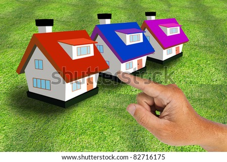 Hand select model house on grass - stock photo
