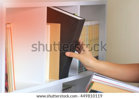 hand selecting the book from a bookshelf