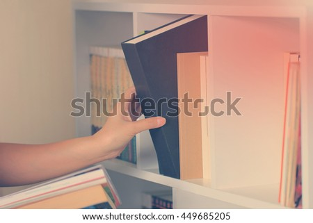 hand selecting the book from a bookshelf, vintage and retro style