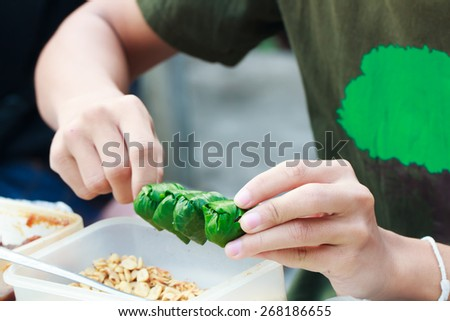 Hand seller made food wrapped in leaves or Miang Kham sold as local market, Thailand - stock photo