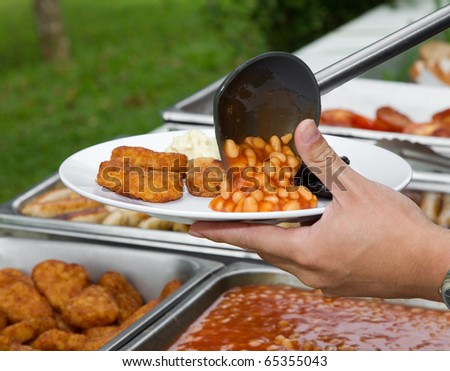 Hand serving a plate of beans and nuggets - stock photo