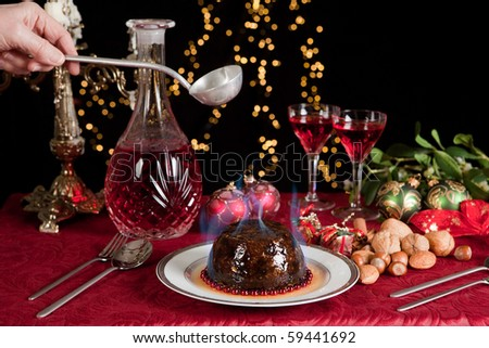 Hand serving burning brandy over a christmas or plum pudding - stock photo