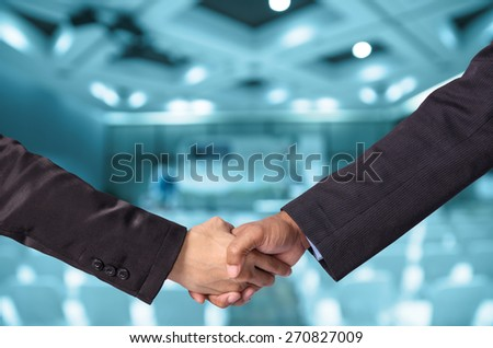 Hand shake between a businessman and a businesswoman o Abstract blurred photo of Meeting preparation at bright conference hall - stock photo