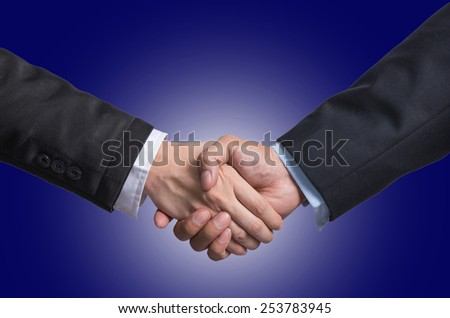 Hand shake between a businessman and a businesswoman on dark blue background - stock photo