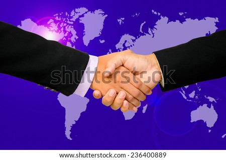 Hand shake between a businessman and a businesswoman on world map. - stock photo