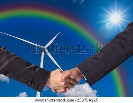 Hand shake between a businessman on Wind turbine power generator background - stock photo