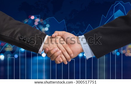 Hand shake between businessman on Trading graph on the cityscape at night and world map background,Business financial concept - stock photo
