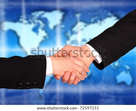 Hand shaking with world map in background - stock photo