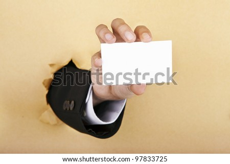 Hand showing a blank business card breaking through a paper wall - stock photo