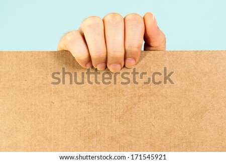 Hand showing a blank cardboard message on blue background - stock photo
