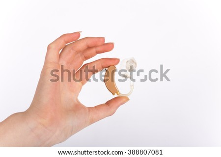Hand showing a hearing aid with ear mould an tubing