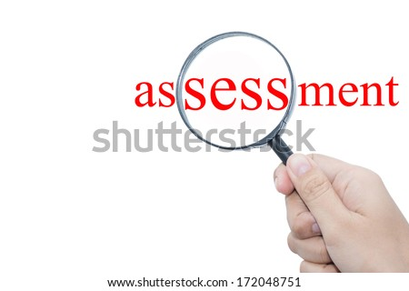 Hand Showing assessment  Word Through Magnifying Glass - stock photo