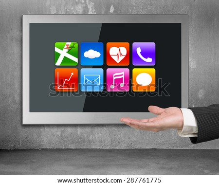 Hand showing black wide flat TV screen with colorful app icons, hanging on concrete wall. - stock photo