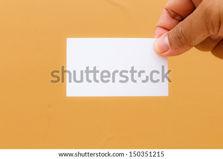 Hand showing blank namecard on yellow background - stock photo