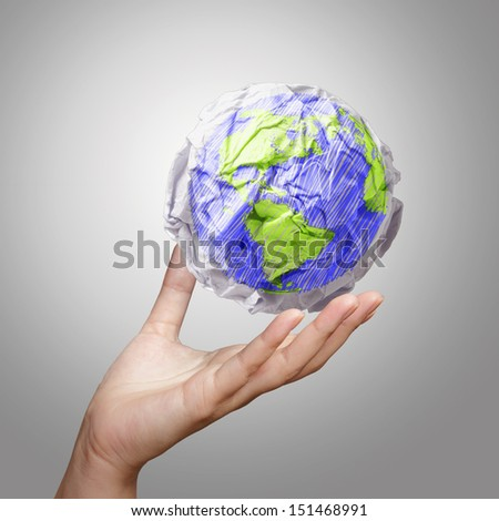 hand showing crumpled world paper symbol as concept