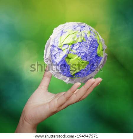 hand showing crumpled world paper symbol as concept on green background - stock photo