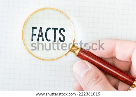 Hand Showing Facts Word Through Magnifying Glass - stock photo