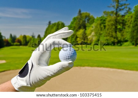 hand showing golf ball over sand bunker at beautiful golf course with blue sky - stock photo