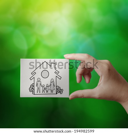hand showing hand drawn house with family icon on canvas board on green nature background as insurance concept  - stock photo