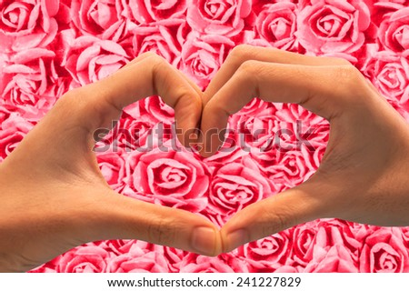 hand showing heart shape gesture on pink roses background.