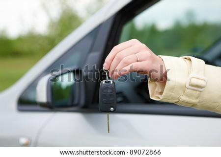 Hand showing keys out the car window - stock photo