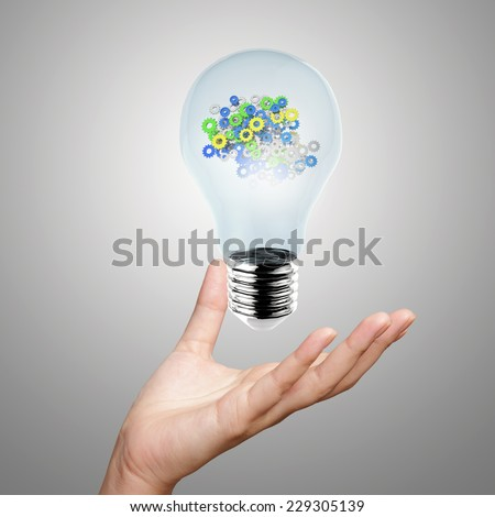 hand showing light bulb with gears as concept - stock photo