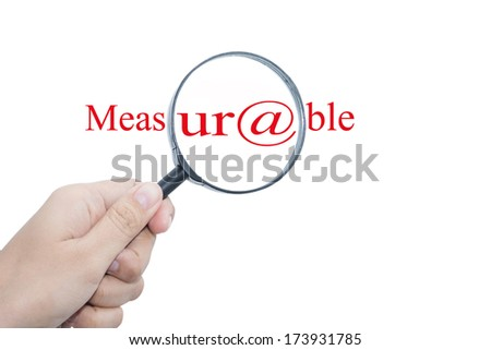 Hand Showing Measurable Word Through Magnifying Glass  - stock photo