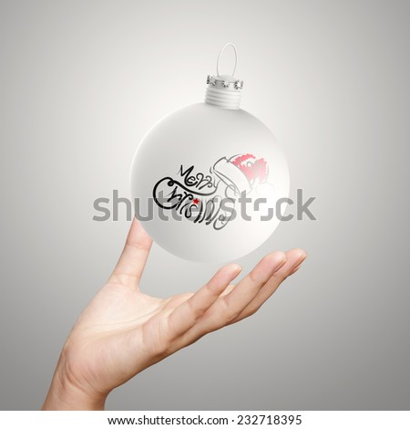 hand showing Merry Christmas in ornament ball - stock photo
