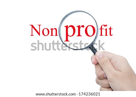 Hand Showing Non profit concept Word Through Magnifying Glass  - stock photo