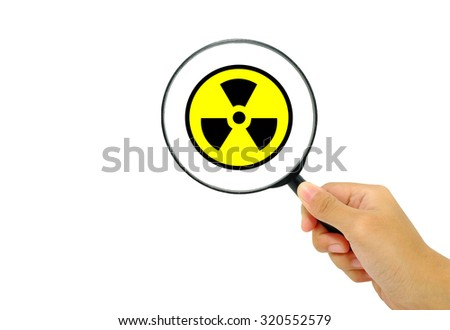 Hand showing radioactive symbol through magnifying glass. - stock photo