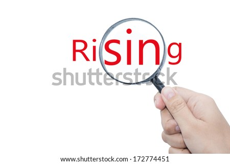 Hand Showing Rising Word Through Magnifying Glass