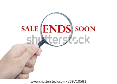 Hand Showing SALE ENDS SOON Word Through Magnifying Glass  - stock photo