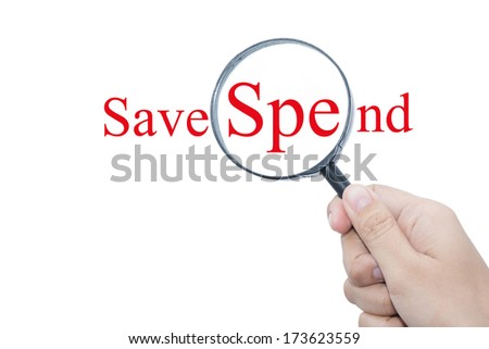 Hand Showing Save Spend Word Through Magnifying Glass   - stock photo