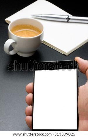 hand showing smartphone with blank screen in foreground and silver pen on notebook and cup of coffee in background - stock photo