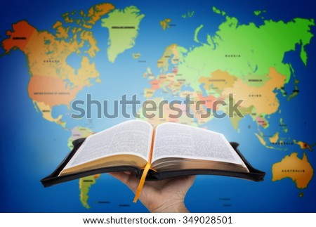Hand showing the Holy Bible against world map - stock photo