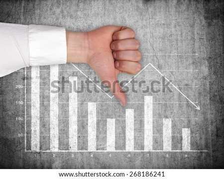 hand showing thumb down  and drawing falling chart on wall - stock photo