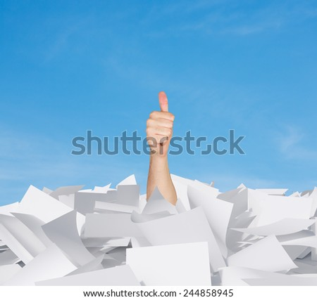 hand showing thumb up in papers heap on a sky background - stock photo