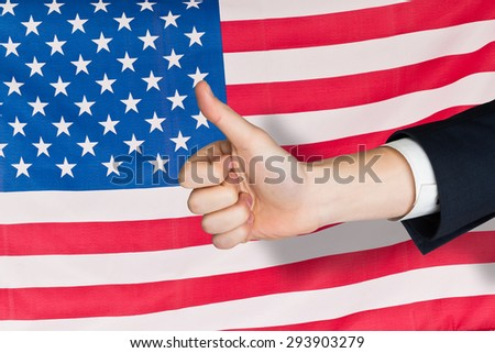 Hand showing thumbs up against rippled us flag