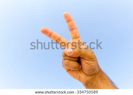 Hand showing thumbs up against the sky - stock photo