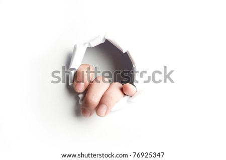 Hand showing trough a hole of a white paper - stock photo
