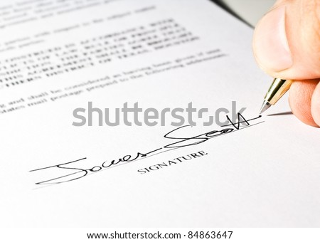Hand signing a contract. The signature is imaginary. - stock photo