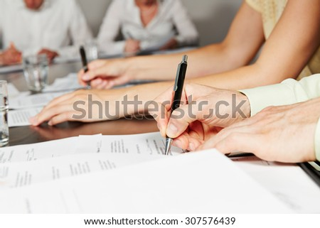 Hand signing contract in business meeting after negotiation - stock photo