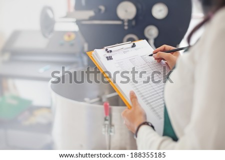 Hand signing document about coffee roasting at factory - stock photo