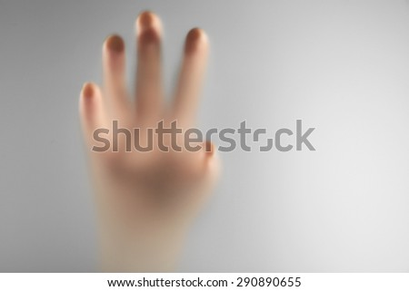 Hand silhouettes behind glass foreground