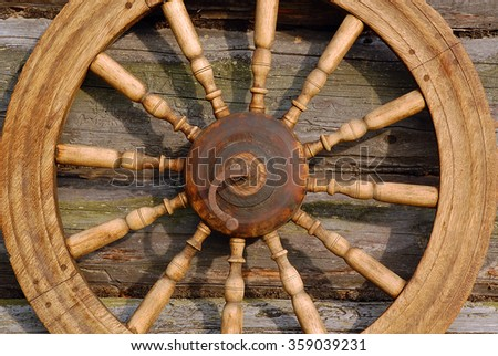 Hand spinning wheel on the wall of the old log house in the Russian village.  - stock photo