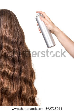 Hand spray varnish long wavy hair young woman isolated on white background. - stock photo