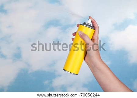 Hand spraying a substance like insecticide into open air - stock photo