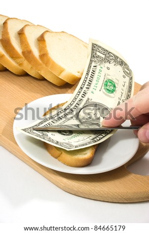 Hand spreads bread with one-dollar banknote on small plate on chopping board