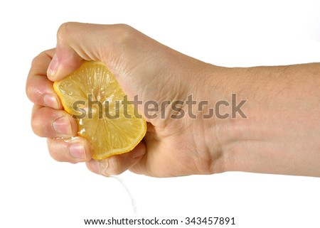 Hand squeezing a lemon isolated on white background