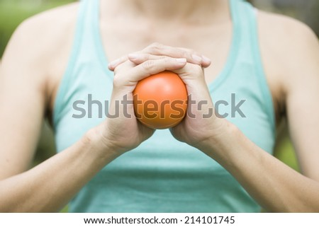 Hand squeezing a stress ball - stock photo